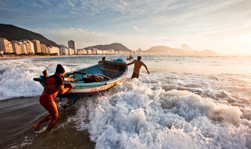 Fishermen launch their boats on Copacabana beach