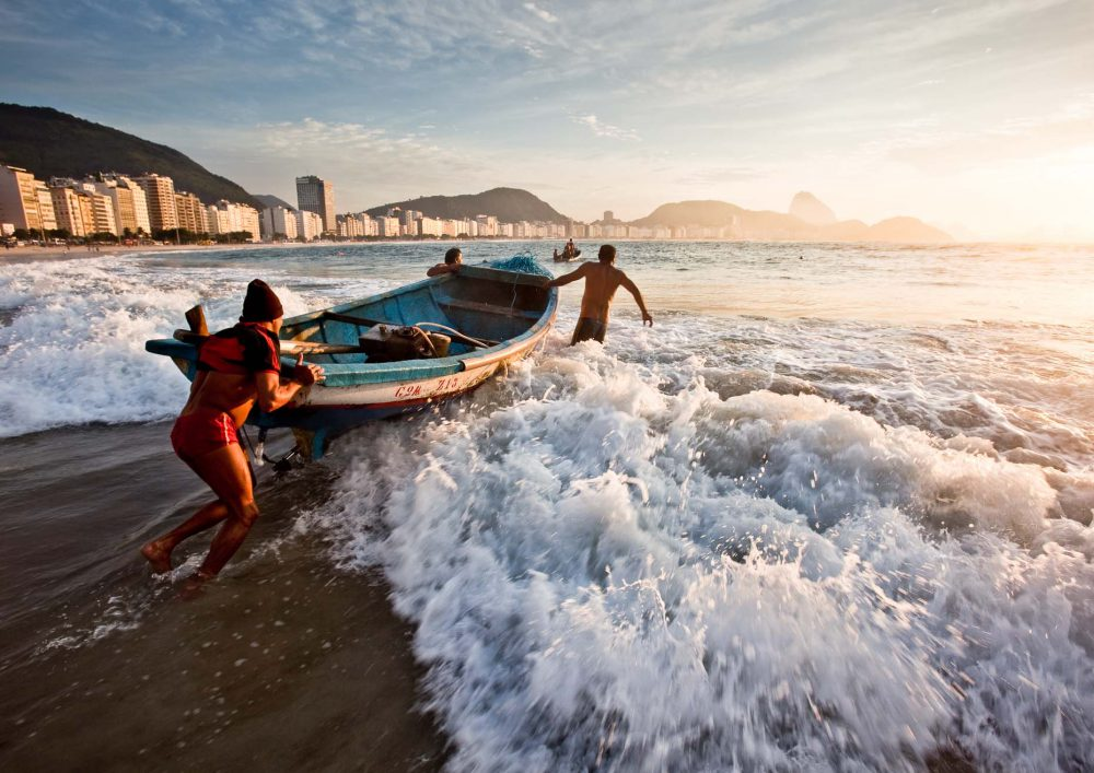 Fishermen launch their boats on Copacabana beach