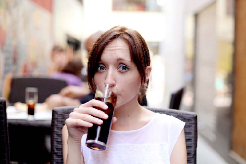 perempuan cantik minum soda di kafe