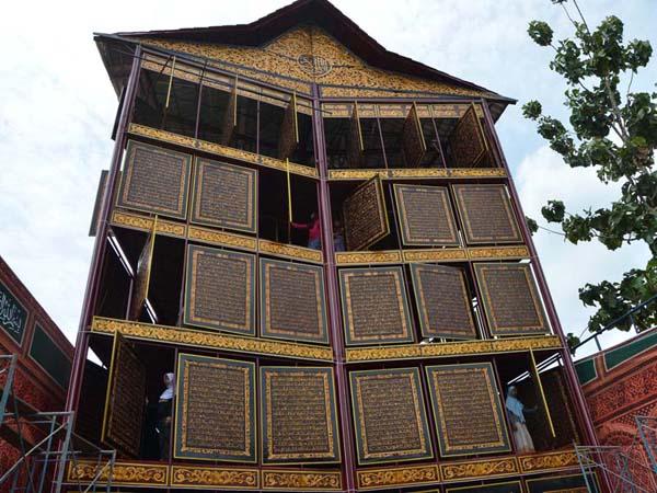 Sejumlah santriwati Ponpes IGM membaca Quran raksasa 30 juz yang dibuat dengan ukiran kayu