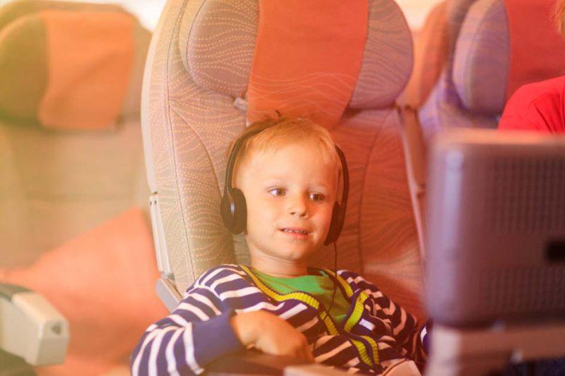 anak kecil memakai headphone di pesawat