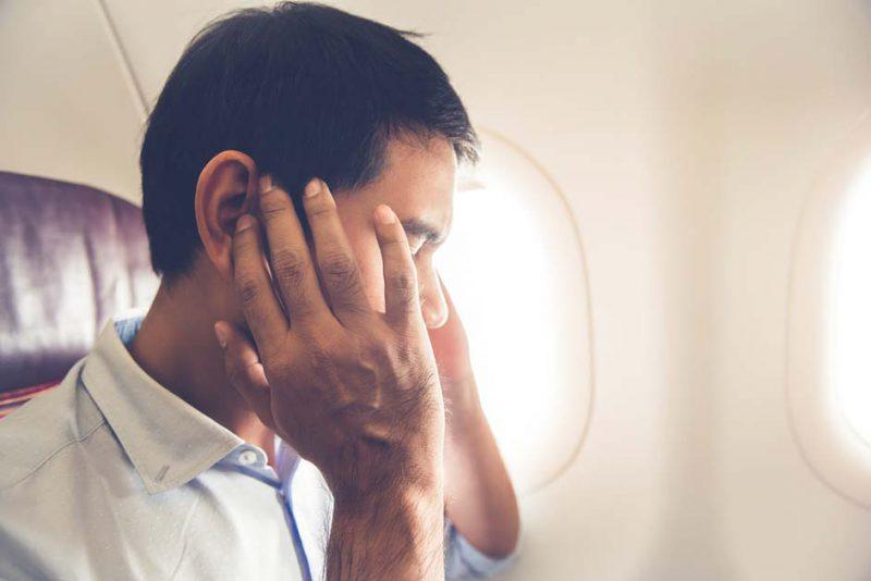 menutup telinga saat pesawat lepas landas