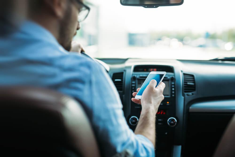 memainkan handphone saat mengemudi